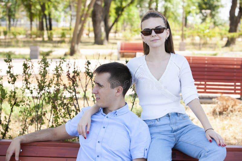 Pares jovenes hermosos que se sientan en un banco en el parque imagenes de archivo
