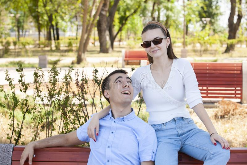 Pares jovenes hermosos que se sientan en un banco en el parque imagen de archivo libre de regalías