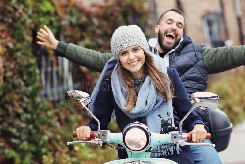 Pares jovenes hermosos que sonríen mientras que monta la vespa en ciudad en otoño foto de archivo