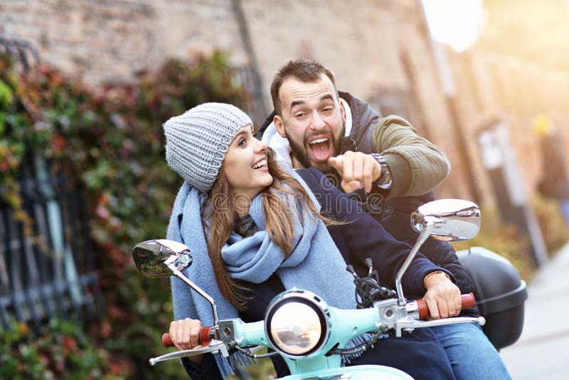 Pares jovenes hermosos que sonríen mientras que monta la vespa en ciudad en otoño imagen de archivo libre de regalías