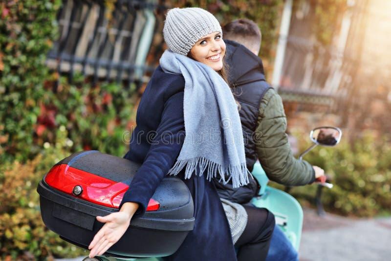 Pares jovenes hermosos que sonríen mientras que monta la vespa en ciudad en otoño fotos de archivo libres de regalías