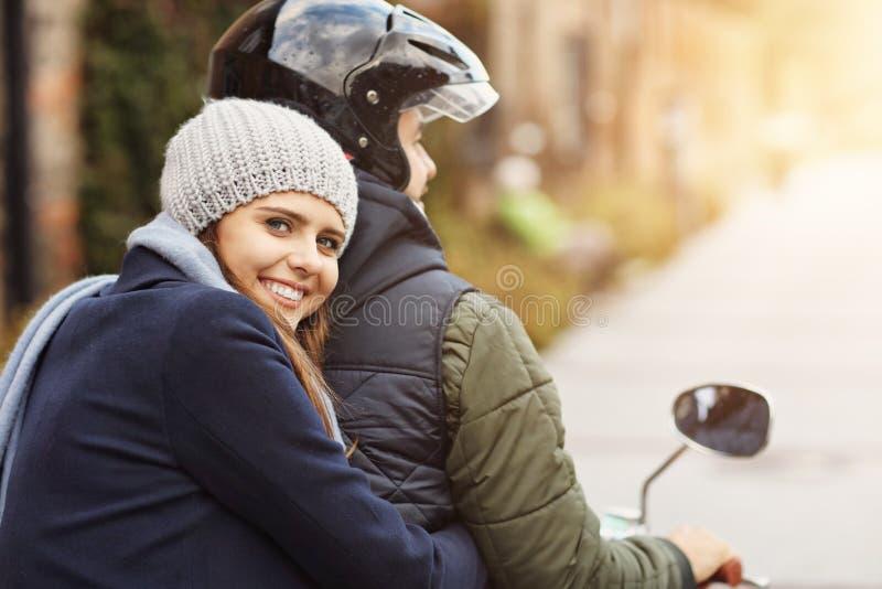 Pares jovenes hermosos que sonríen mientras que monta la vespa en ciudad en otoño imagen de archivo