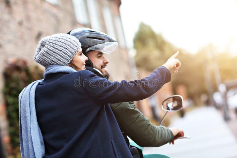 Pares jovenes hermosos que sonríen mientras que monta la vespa en ciudad en otoño fotografía de archivo libre de regalías