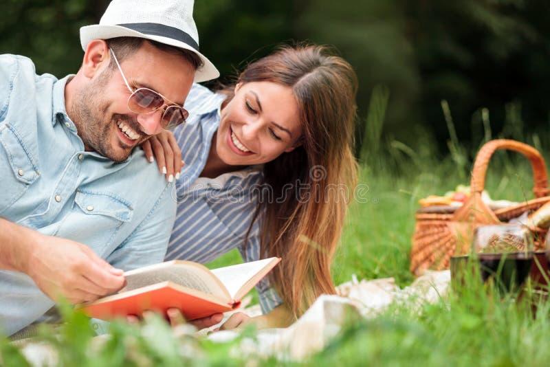 Pares jovenes hermosos que tienen una comida campestre romántica relajante en un parque imágenes de archivo libres de regalías