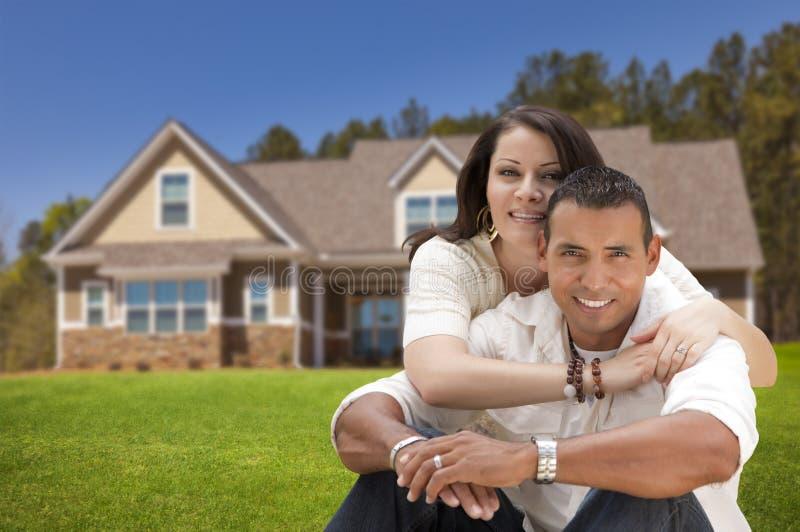 Pares jovenes hispánicos felices delante de su nuevo hogar imágenes de archivo libres de regalías
