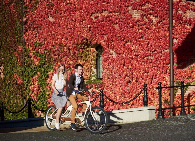 Pares jovenes, hombre hermoso y mujer rubia completando un ciclo la bici en t?ndem construyendo demasiado grande para su edad con fotografía de archivo libre de regalías