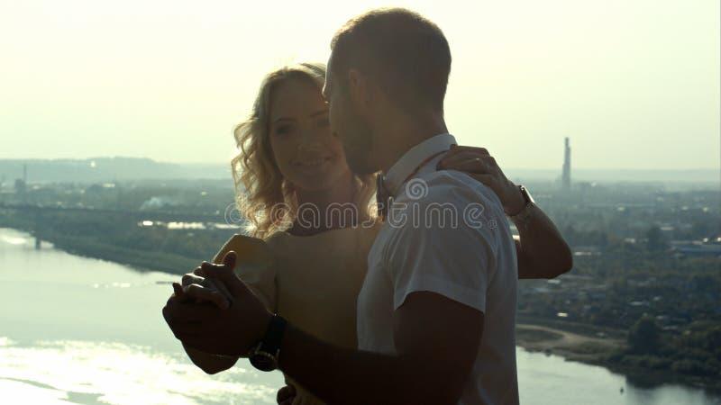 Pares jovenes, individuo que detiene a la mujer en los brazos, mirando uno a, actitud de la danza imagenes de archivo