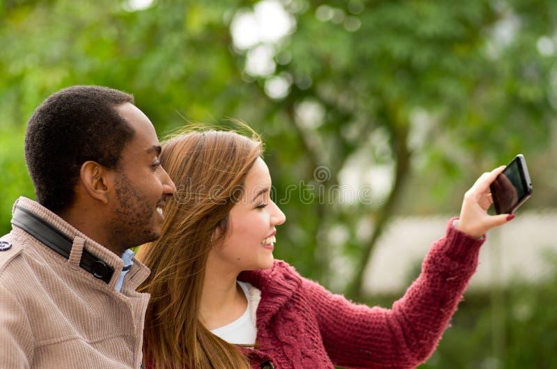 Pares jovenes interraciales felices hermosos y sonrientes en el parl que toma un selfie fotos de archivo libres de regalías