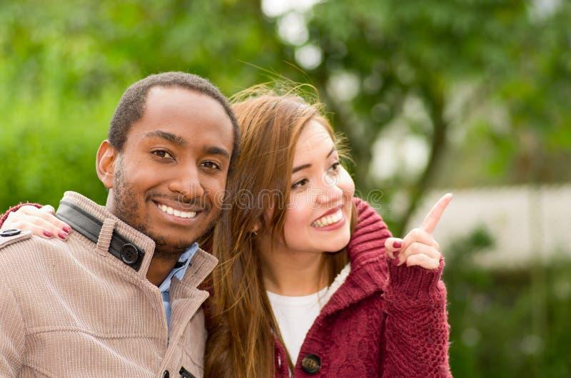 Pares jovenes interraciales felices hermosos y sonrientes en el parque, mujer que señala en alguna parte en un fondo del parque fotografía de archivo