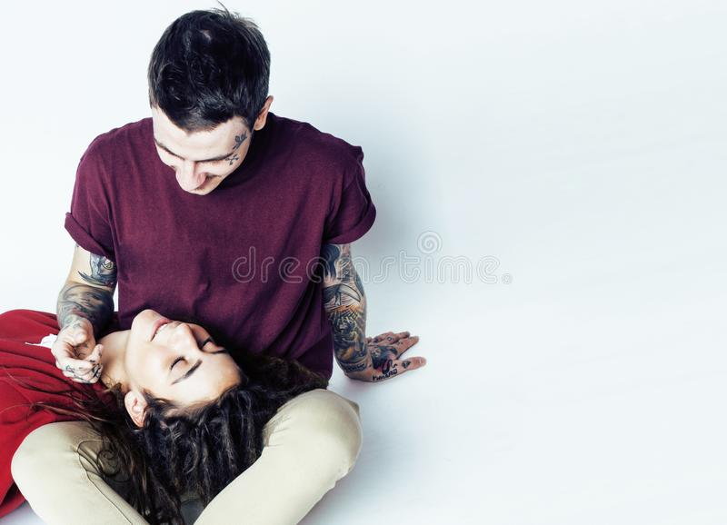 Pares jovenes junto individuo con el tatuaje, dreadlocks que llevan de la novia que se divierten en el fondo blanco fotografía de archivo
