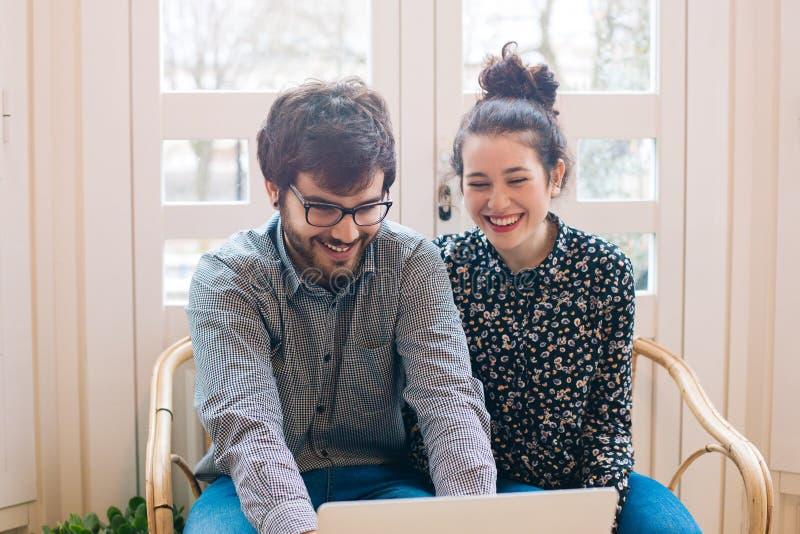 Pares jovenes lindos con el ordenador portátil foto de archivo