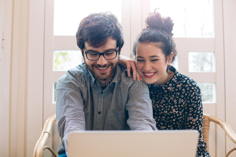Pares jovenes lindos con el ordenador portátil fotos de archivo
