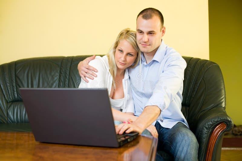 Pares jovenes lindos con la computadora portátil en el país. foto de archivo