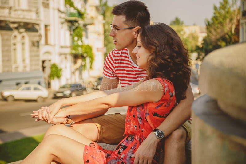 Pares jovenes lindos en el abrazo del amor, sentándose al aire libre en la calle verde de la ciudad, verano imágenes de archivo libres de regalías