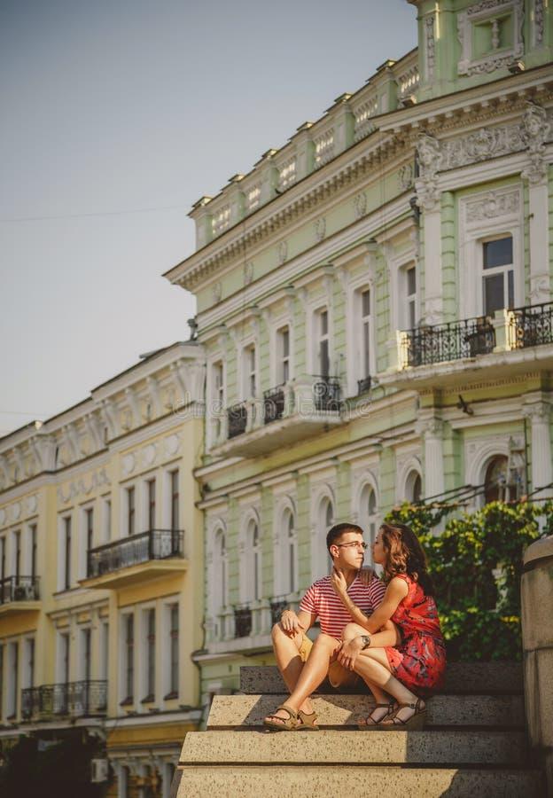 Pares jovenes lindos en el abrazo del amor, sentándose en las escaleras al aire libre en la calle verde de la ciudad, verano fotos de archivo libres de regalías