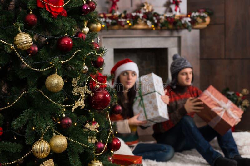 Pares jovenes lindos que conjeturan en sus regalos de la Navidad que detienen a BO fotos de archivo