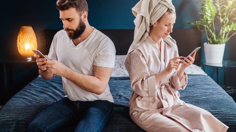 Pares jovenes, mujer en albornoz y toalla en su cabeza, sentándose en cama, usando smartphone Muchacha e individuo que comprueban imagen de archivo libre de regalías