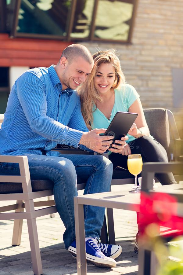 Pares jovenes, mujer y hombre, en café y jugo de consumición del café de la calle mientras que mira imágenes de días de fiesta imagen de archivo libre de regalías