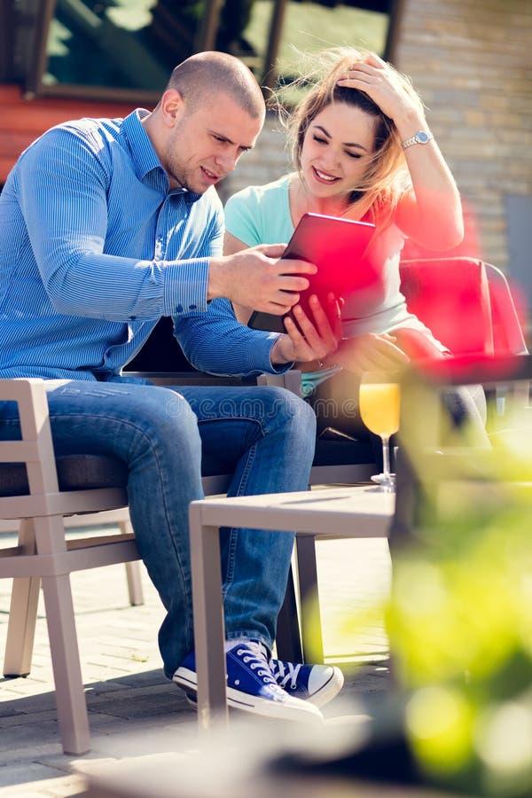 Pares jovenes, mujer y hombre, en café y jugo de consumición del café de la calle mientras que mira imágenes de días de fiesta fotos de archivo libres de regalías