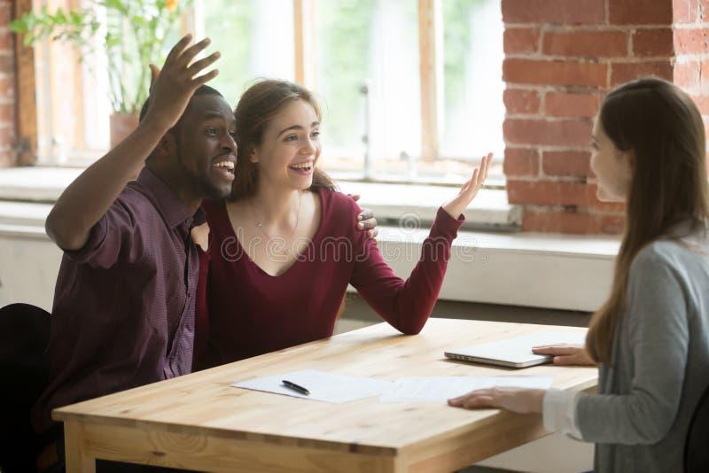 Pares jovenes multiétnicos felices de oír buen trato del agente inmobiliario foto de archivo libre de regalías