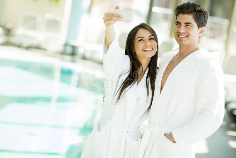 Pares jovenes por la piscina imagen de archivo libre de regalías