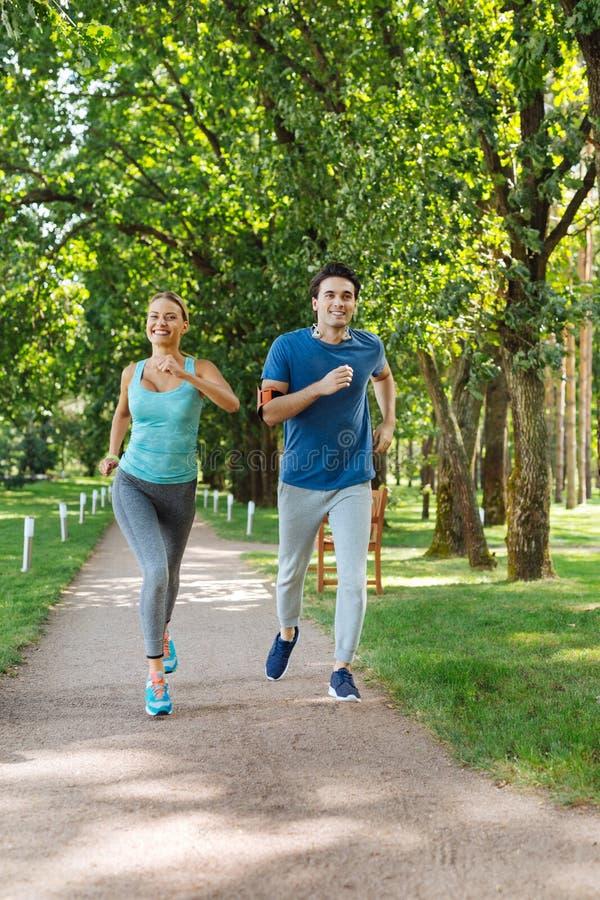 Pares jovenes positivos agradables que corren al aire libre junto foto de archivo libre de regalías