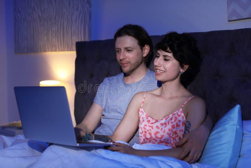 Pares jovenes preciosos con el ordenador portátil en cama imágenes de archivo libres de regalías