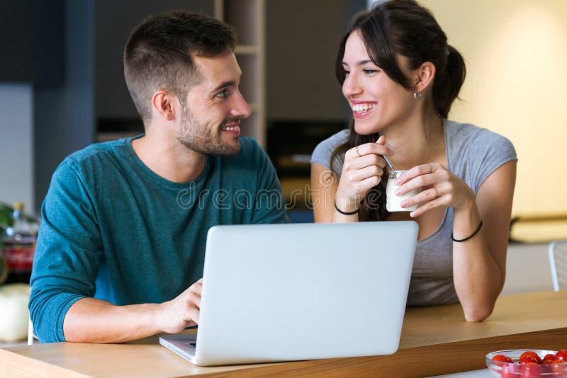 Pares jovenes preciosos hermosos usando su ordenador portátil y desayuno el tener en la cocina en casa fotos de archivo libres de regalías