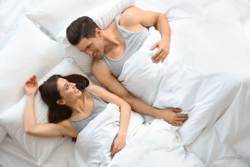 Pares jovenes preciosos que descansan en cama grande, arriba foto de archivo