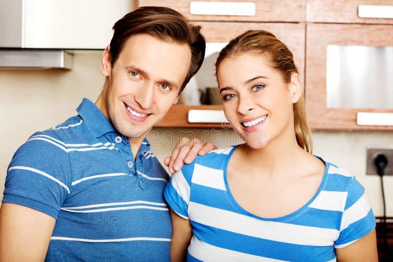 Pares jovenes preciosos que se colocan en cocina imagen de archivo