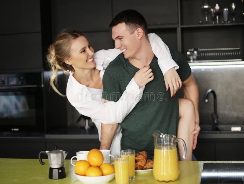 Pares jovenes preciosos que se colocan y que abrazan en una cocina en casa fotografía de archivo