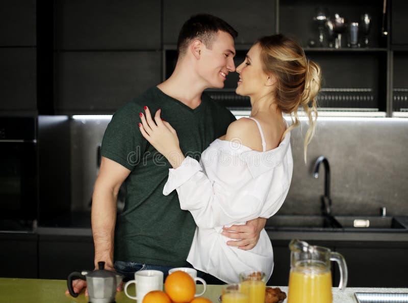 Pares jovenes preciosos que se colocan y que abrazan en una cocina en casa imagen de archivo libre de regalías