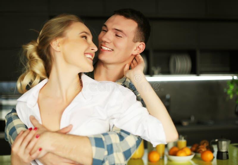Pares jovenes preciosos que se colocan y que abrazan en una cocina en casa fotos de archivo