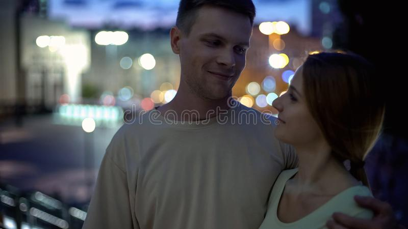 Pares jovenes que abrazan contra el fondo de la ciudad de la noche, sentido de la comodidad de la confiabilidad fotos de archivo