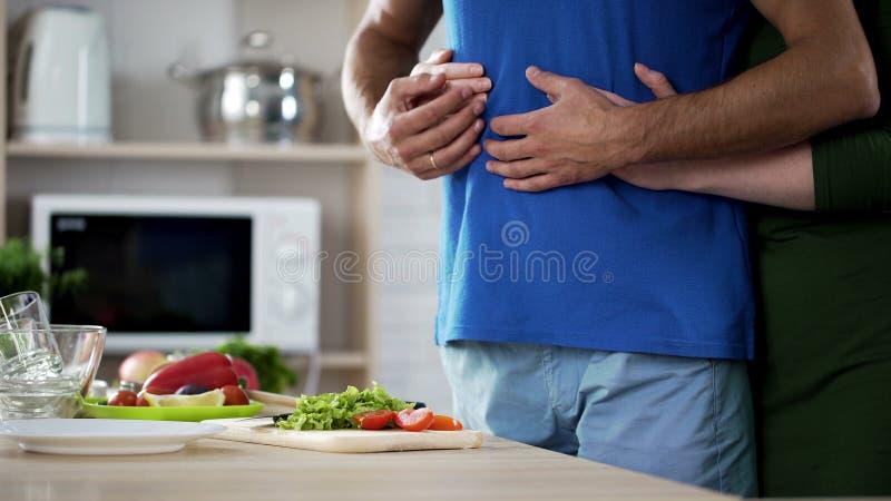 Pares jovenes que abrazan durante la preparación de la cena en cocina, cuidado y ayuda fotos de archivo libres de regalías