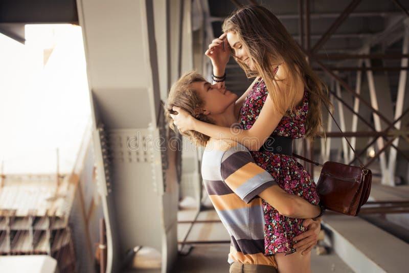 Pares jovenes que abrazan en la luz del día del verano en un construc del puente fotos de archivo libres de regalías