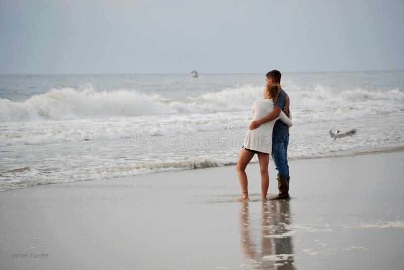Pares jovenes que abrazan en la playa imágenes de archivo libres de regalías