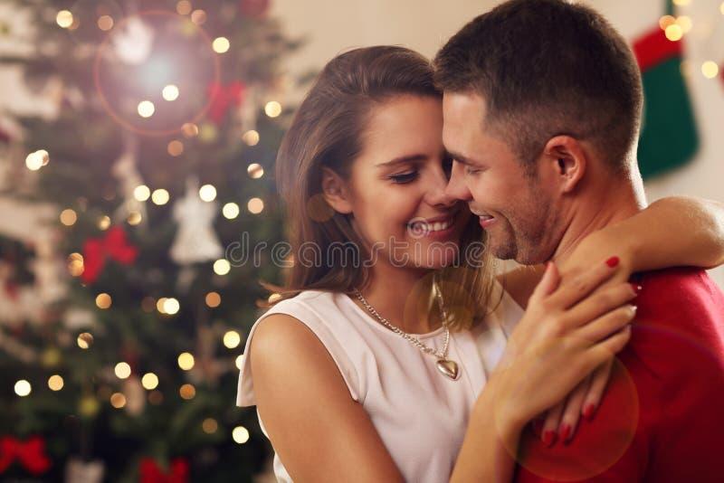 Pares jovenes que abrazan en tiempo de la Navidad fotos de archivo