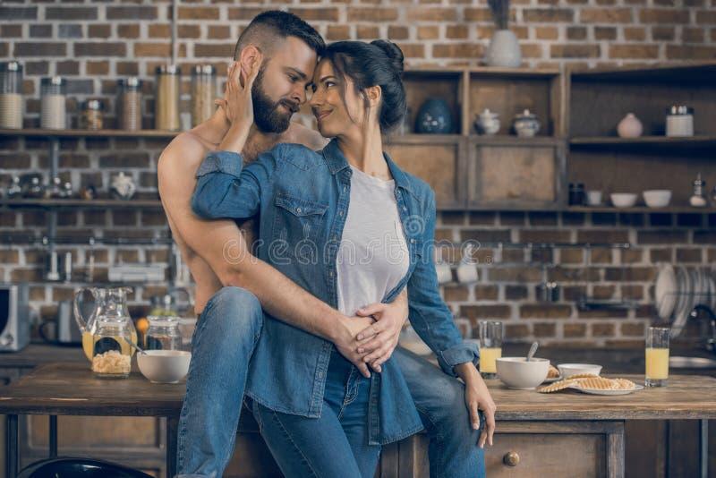 Pares jovenes que abrazan mientras que desayunando en casa imágenes de archivo libres de regalías