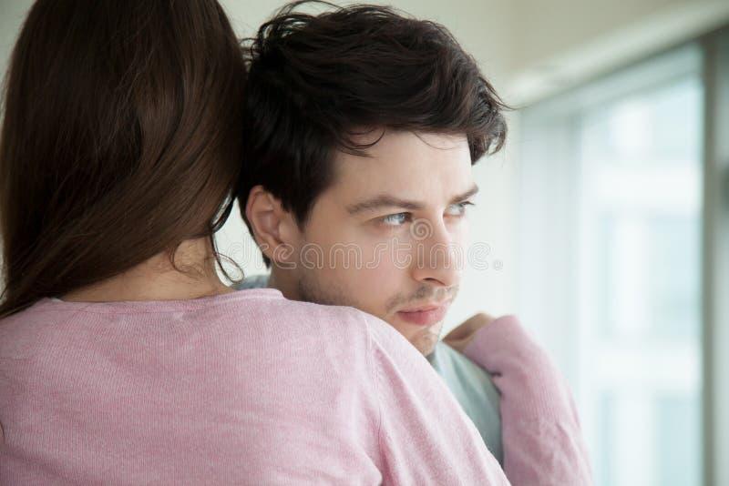Pares jovenes que abrazan, mujer que abraza confortando al hombre, conso de la esposa imagen de archivo libre de regalías