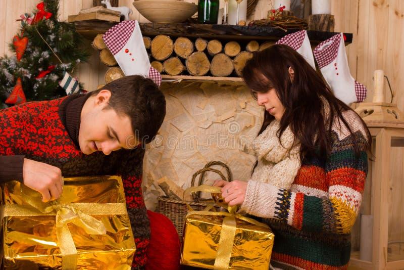 Pares jovenes que abren los regalos festivos de Navidad del oro fotos de archivo libres de regalías