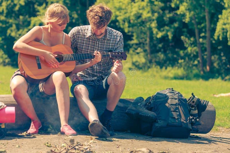 Pares jovenes que acampan tocando la guitarra al aire libre imágenes de archivo libres de regalías