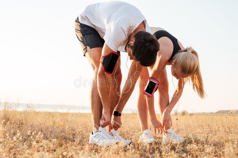 Pares jovenes que atan sus zapatos y que consiguen listos para correr imagen de archivo libre de regalías