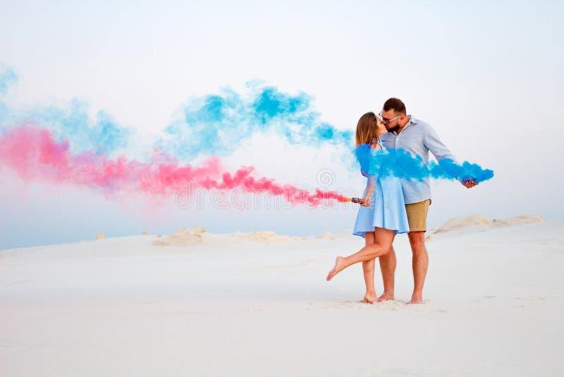 Pares jovenes que besan y que sostienen humo coloreado en manos, pares románticos con color azul y la bomba de humo del color roj fotografía de archivo libre de regalías