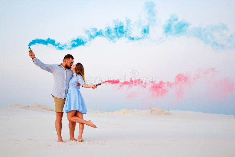 Pares jovenes que besan y que sostienen humo coloreado en manos, pares románticos con color azul y la bomba de humo del color roj imagenes de archivo