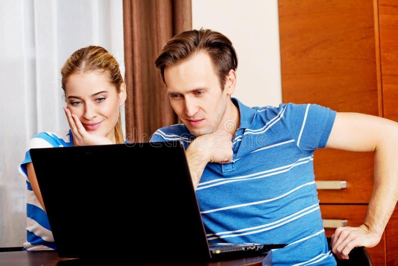 Pares jovenes que buscan algo en el ordenador portátil imagen de archivo libre de regalías