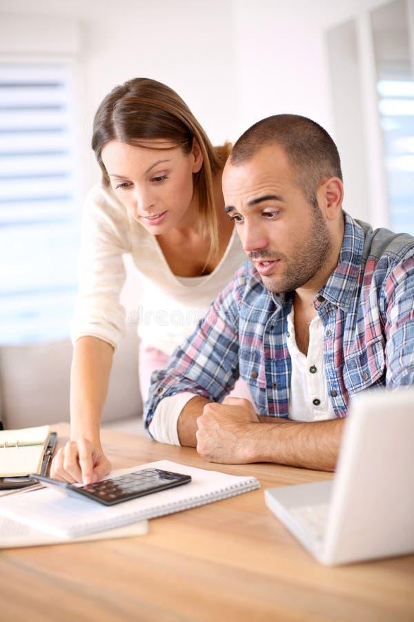Pares jovenes que calculan su presupuesto foto de archivo libre de regalías
