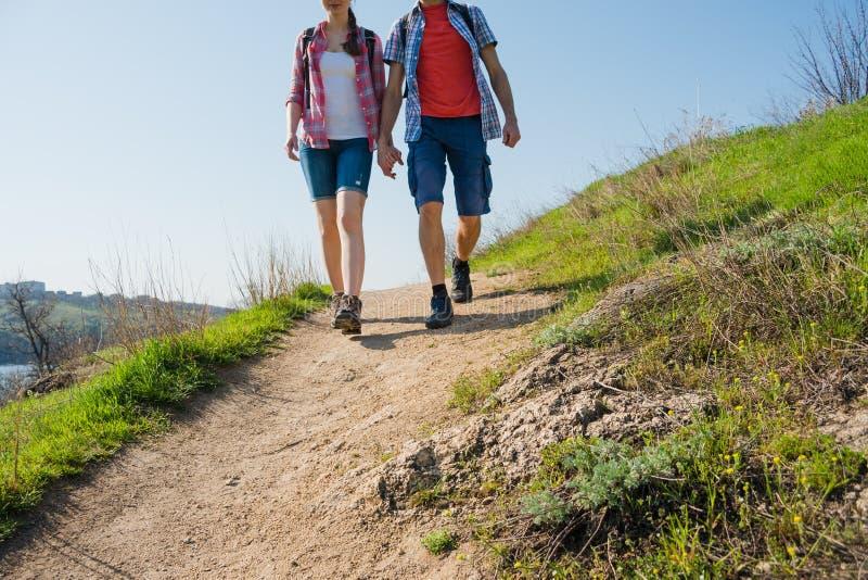 Pares jovenes que caminan con las mochilas en Rocky Trail hermoso en Sunny Evening Viaje y aventura de la familia imagen de archivo libre de regalías