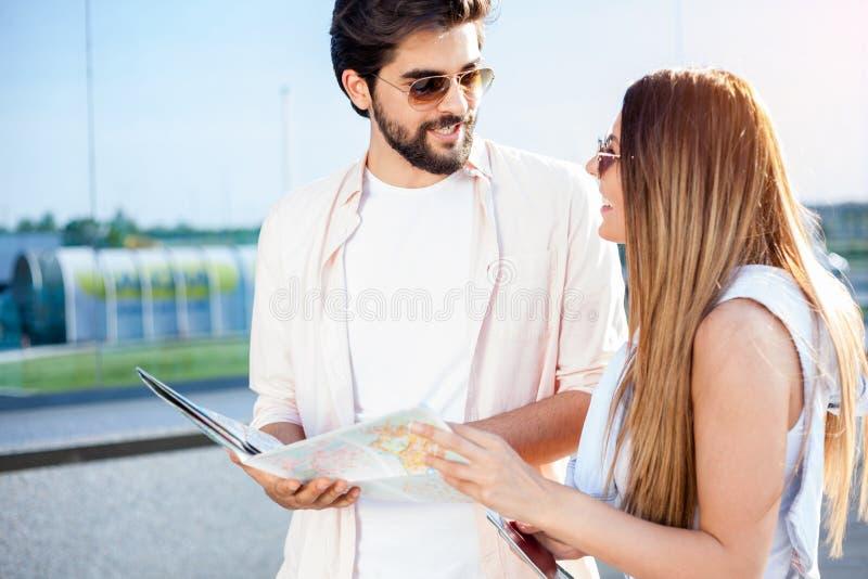 Pares jovenes que caminan delante de una terminal de aeropuerto, tirando de las maletas fotos de archivo libres de regalías