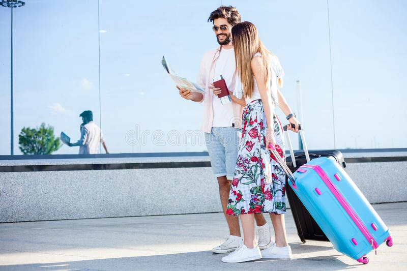 Pares jovenes que caminan delante de una terminal de aeropuerto, tirando de las maletas foto de archivo libre de regalías